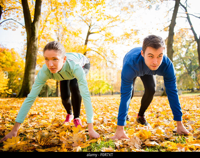 Young couple in starting position prepared for running in autumn nature - Stock Image