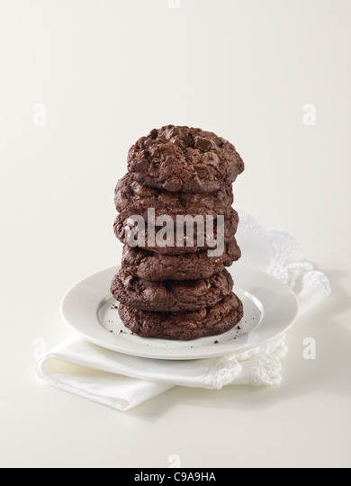 A tall stack of gourmet triple chocolate chip cookies on a white plate - Stock Image