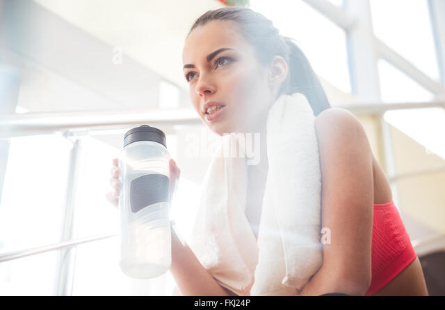 Pretty young sportswoman relaxing after training and drinking water in gym - Stock-Bilder