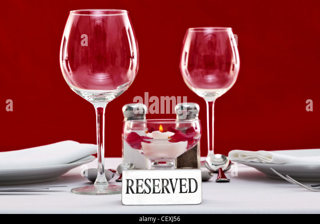 Photo of a Reserved sign on a restaurant table with red background. - Stock Image