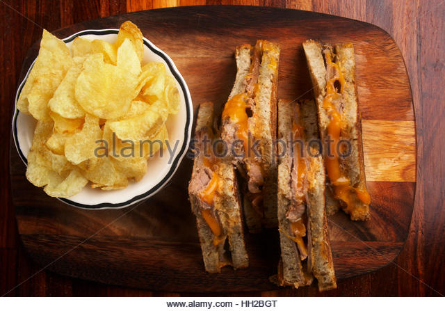 Pastrami Reuben with cheddar cheese and home made potato chips - Stock Image