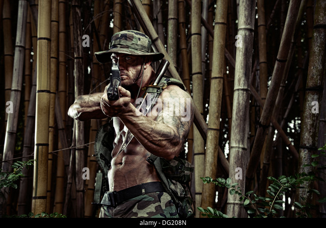 Soldier with knife and rifle in bamboo forest - Stock-Bilder