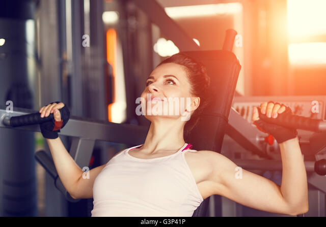 Young smiling woman doing chest fly exercise on gym machine. - Stock-Bilder