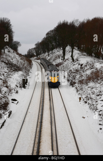 A high speed Hitachi Javelin train rushing through the snowy Kent winter countryside in England - Stock Image
