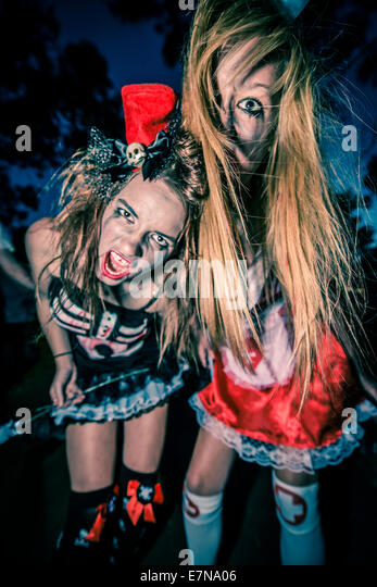 Zombies prowl the night during an annual zombie walk - Stock Image