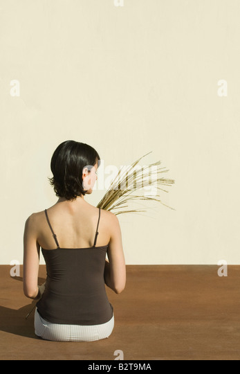 Woman sitting on the ground, holding wheat stalks, rear view - Stock-Bilder