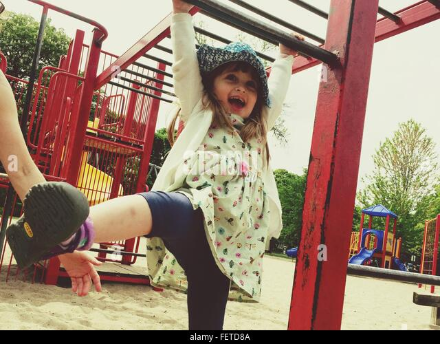 Happy Girl Playing At Jungle Gym In Park - Stock-Bilder