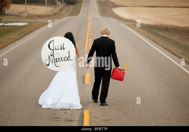 three hills, alberta, canada; a bride and groom walking down a  road holding a jerry can and a parasol saying 'just - Stock Image
