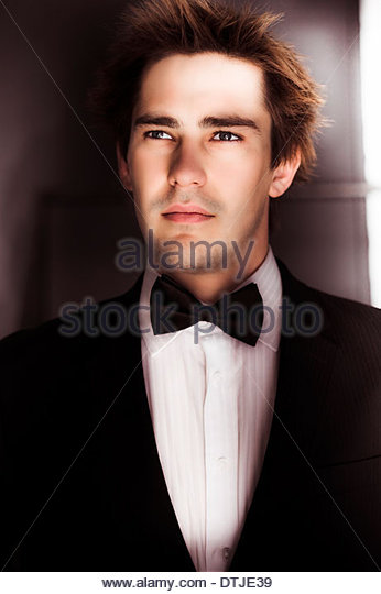 Half Body Portrait Of A Covert And Undercover Secret Agent Dressed As A Butler In Bow Tie Tuxedo When On A Clandestine - Stock Image