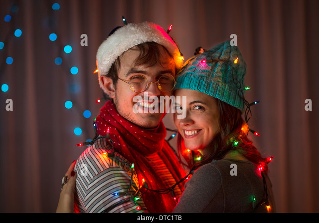 Young couple wrapped in decorative lights at christmas - Stock Image