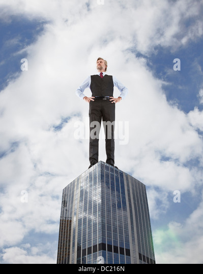 Oversized businessman standing on skyscraper, low angle view - Stock Image