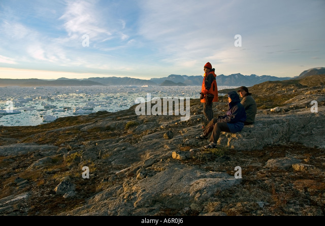 Watching the sunset at Paornakajît, Sermilik Fjord, East Greenland - Stock Image
