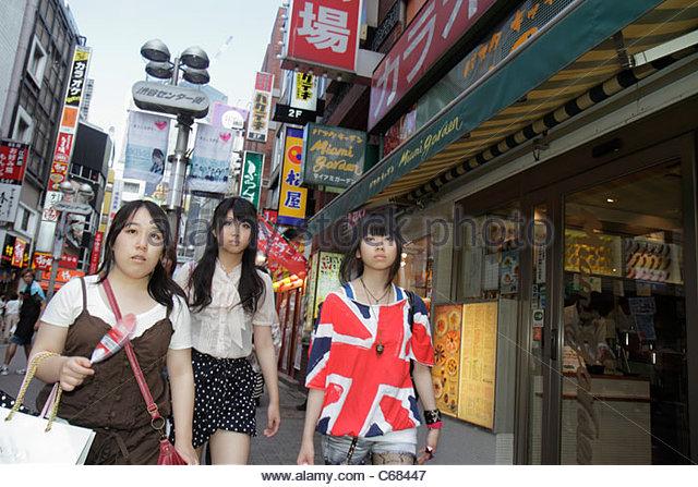 Tokyo Japan Shibuya kanji hiragana katakana characters symbols Japanese English shopping business signs pedestrian - Stock Image