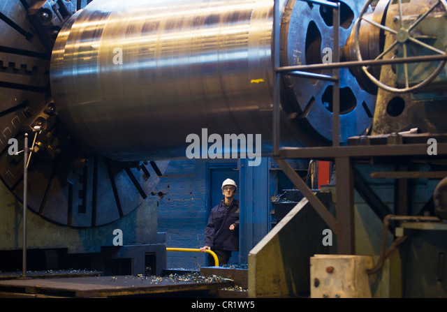 Worker with machinery in steel forge - Stock Image