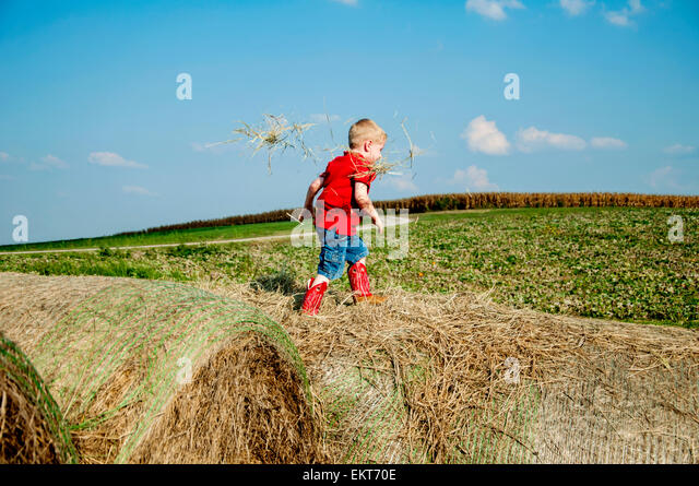 Boy walking on haybales - Stock Image