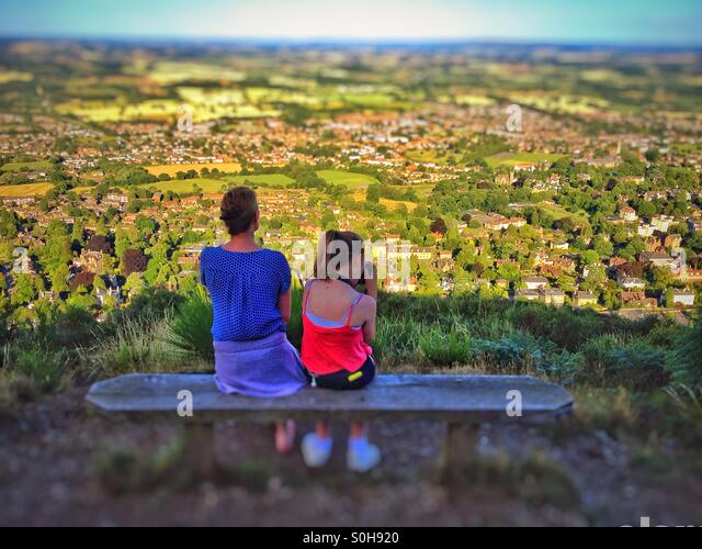 Woman and daughter sitting on a bench overlooking Malvern UK - Stock Image