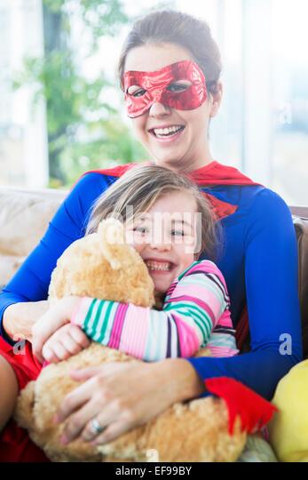 Superhero mother hugging daughter on sofa - Stock Image