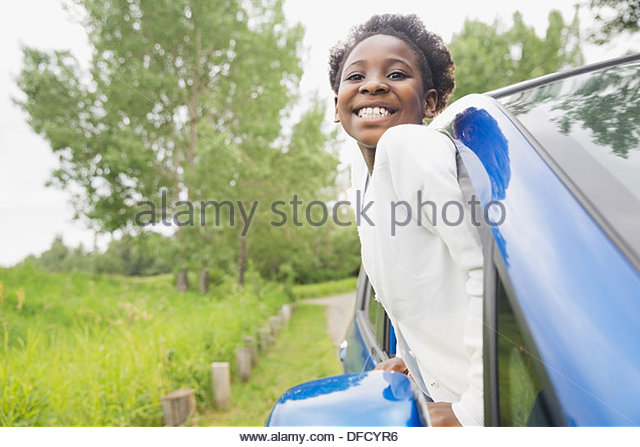 Cheerful girl looking out of car window - Stock Image