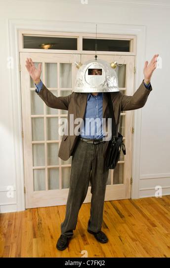 man wearing helmet with antennas reaching upward - Stock Image