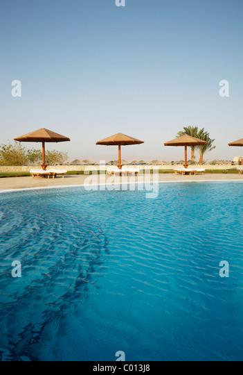 Pool with a blue water surface, sun lounges and sunshades, Soma Bay, Red Sea, Egypt, Africa - Stock Image