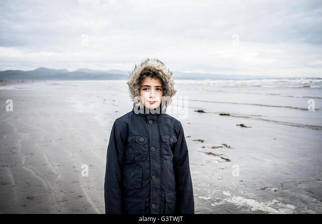 A young boy standing on the beach at Porthmadog. - Stock-Bilder