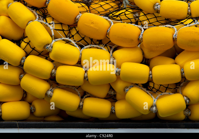 Bright yellow corks and  commercial fishing seine net stacked on deck the of a vessel in Auke Bay, near Juneau, - Stock Image
