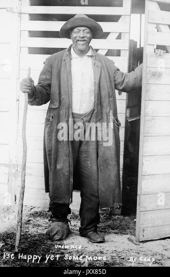 Full length standing portrait of a smiling mature African American man standing in front of a set of doors, carrying - Stock Image