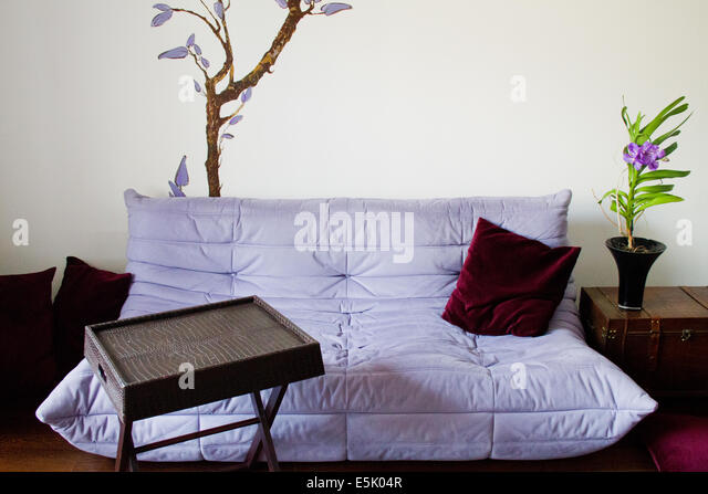Minimalist living design with purple sofa, wooden box and elegant decorations - Stock Image