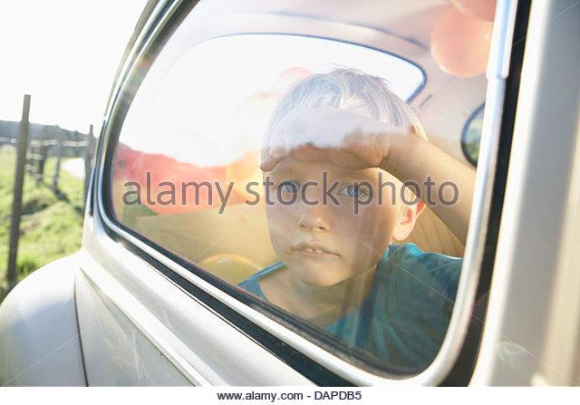Germany, North Rhine Westphalia, Cologne, Boy in car looking through window - Stock Image