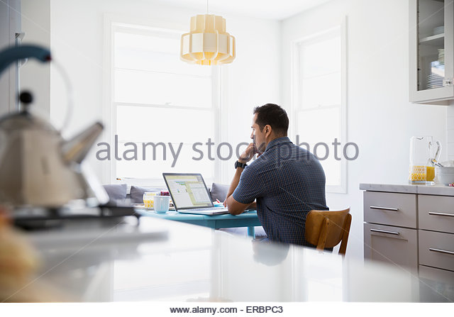 Serious brunette man using laptop at kitchen table - Stock-Bilder
