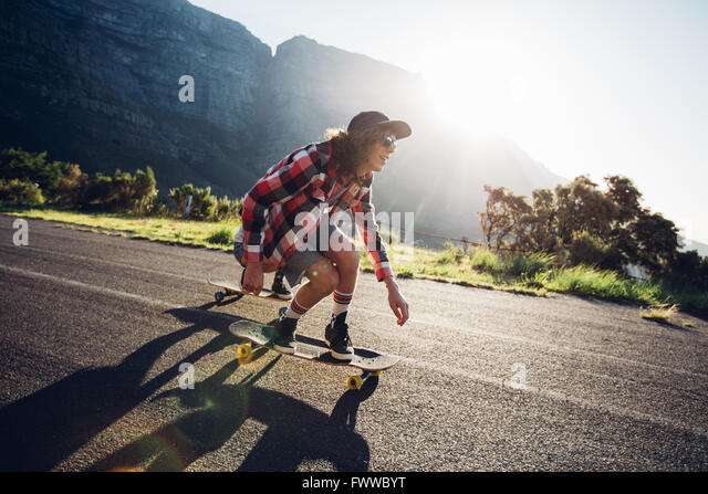 Young man longboarding outdoors on countryside road. Male skateboarding on a sunny day. - Stock Image