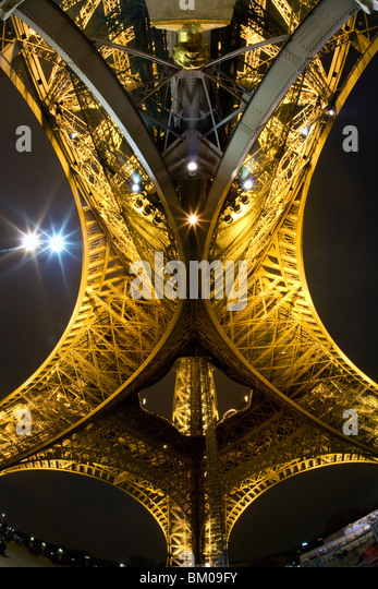 View from the bottom of the Eiffel Tower at night - Stock Image