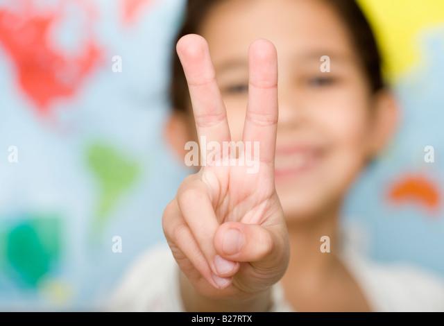 Child making peace sign hand gesture - Stock-Bilder
