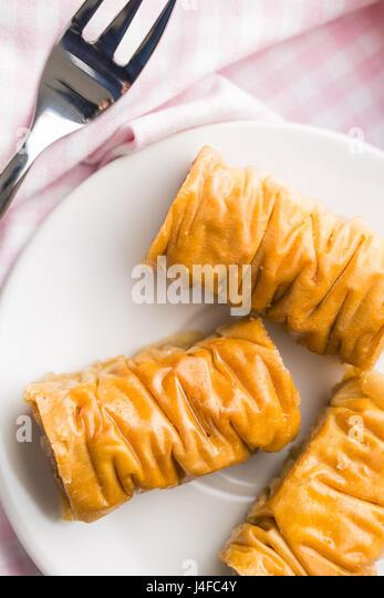 Sweet dessert baklava on white dessert plate. Top view. - Stock Image