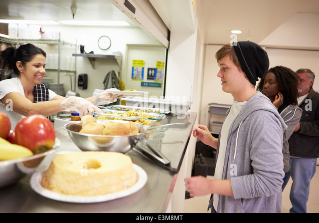 Kitchen Serving Food In Homeless Shelter - Stock Image