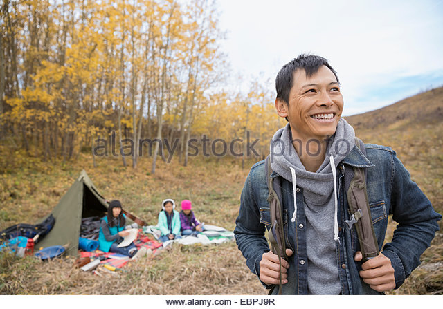 Smiling man camping with family - Stock-Bilder
