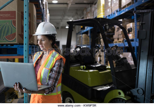 Female worker using laptop next to forklift in distribution warehouse - Stock Image