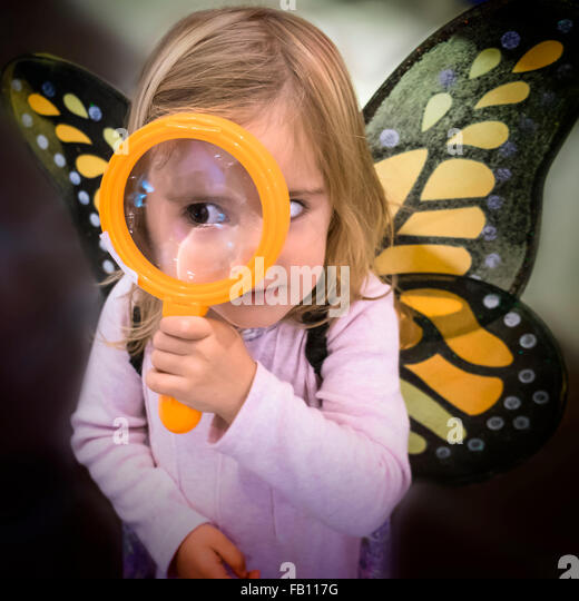 Girl (2-3) wearing butterfly wings looking through magnifying glass - Stock-Bilder
