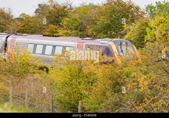 An Inter City train passes through the countryside screened by hedgerows and trees, England, UK - Stock Image