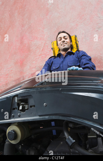 Portrait of an auto mechanic repairing a car in a garage - Stock Image