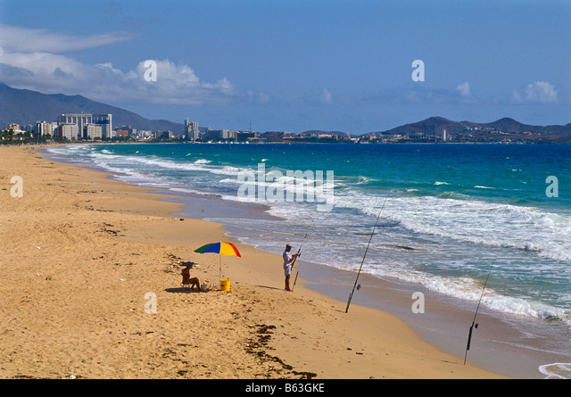 Venezuela beach with surf fishermen near Porlimar City Isla Margarita island south america tourism south american - Stock Image