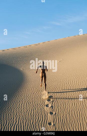 Nude woman running in desert leaving footprints - Stock Image