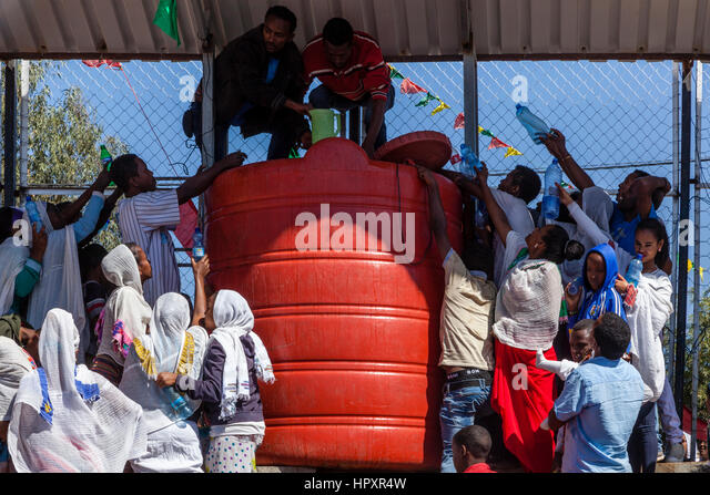 Ethiopian Christians Hold Plastic Bottles Up To Be Filled With Holy Water During The Timkat (Epiphany) Celebrations, - Stock Image