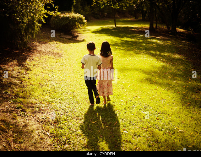 Golden hour: boy and girl summer afternoon walk in woods - Stock Image