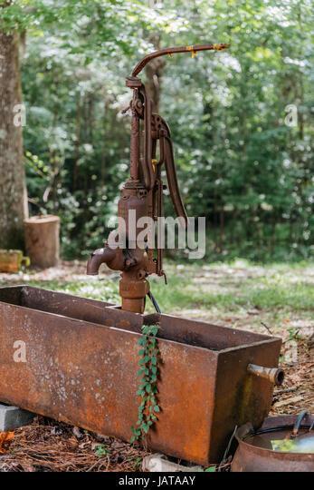Old style rusty hand pump and water trough in rural setting. - Stock Image