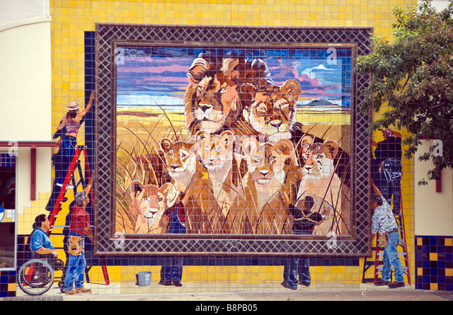 Outdoor mural art San Antonio Texas shows workers hanging mural of African lion pride - Stock Image