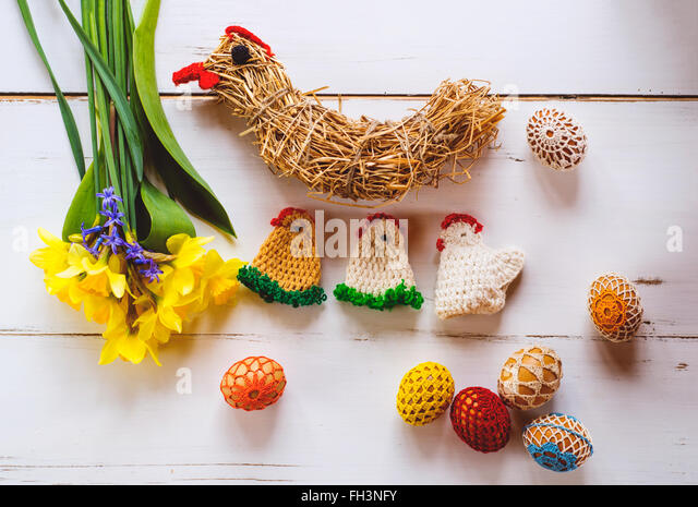 Crocheted Easter eggs, chickens and daffodils, wooden background - Stock-Bilder