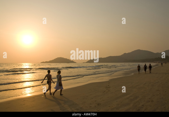People walking along Palolem beach in Goa in South India at sunset - Stock Image