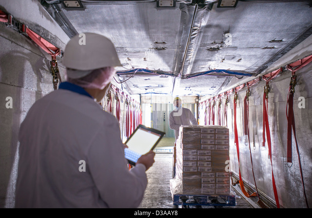 Worker checking products into freezer truck of food factory with tablet - Stock Image