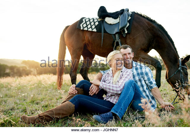 Laughing couple enjoying a romantic moment while sitting together in a field next to their horse on a sunny afternoon - Stock Image